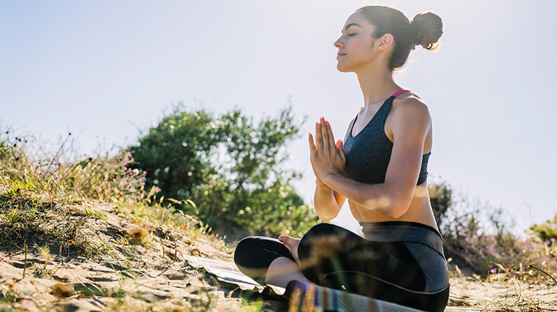 practicar yoga en la playa, meditación